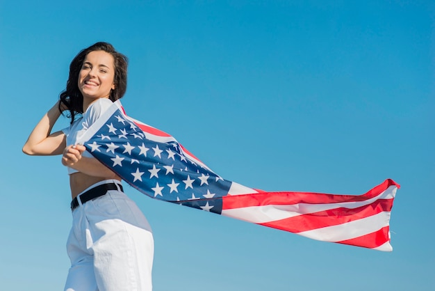 Lächelnde frau, die große usa-flagge wie umhang trägt