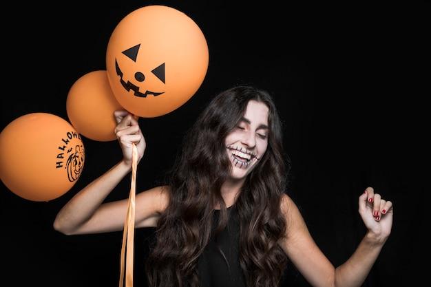 Lächelnde frau, die halloween-ballone und -tanzen hält