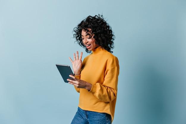 Lächelnde frau, die hand am digitalen tablettbildschirm winkt