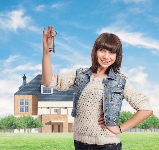 Lächelnde frau, die hausschlüssel von ihrem neuen zuhause