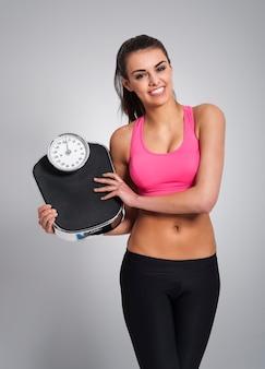 Lächelnde frau, die ihr gewicht kontrolliert