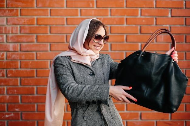 Lächelnde frau, die ihre handtasche zu bewundern
