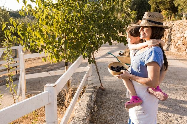 Lächelnde frau, die ihre tochter hält geerntete oliven in der schüssel trägt