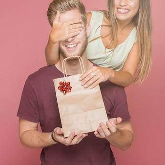 Lächelnde frau, die ihrem freund einkaufsgeschenkbeutel gibt