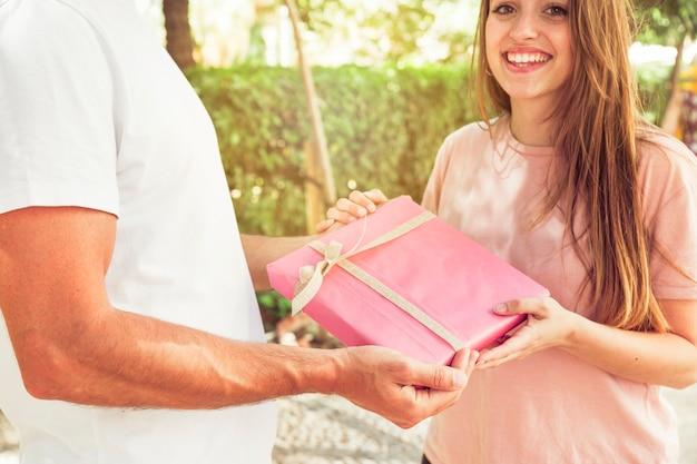 Lächelnde frau, die ihrem freund valentinsgrußgeschenk gibt