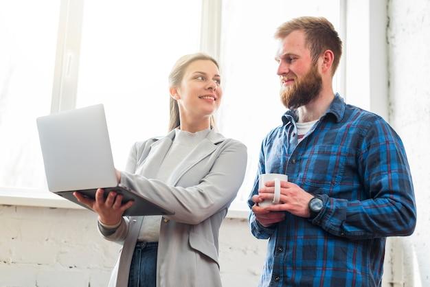 Lächelnde frau, die ihrem kollegen laptop am arbeitsplatz zeigt