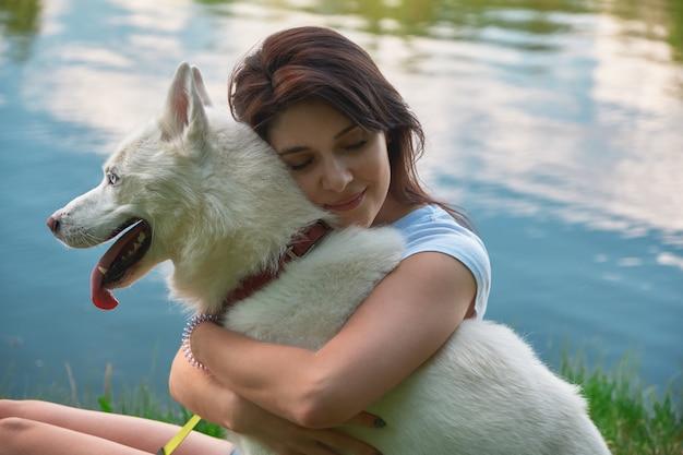 Lächelnde frau, die ihren hund umarmt