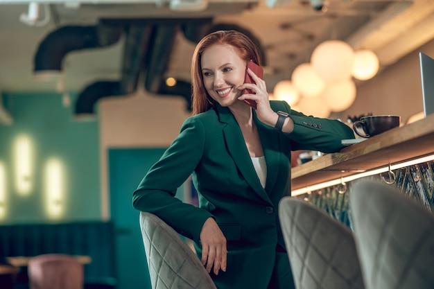Lächelnde frau, die im café auf dem smartphone spricht