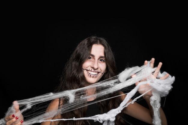 Lächelnde frau, die im gefälschten spinnennetz verwirrt