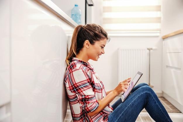 Lächelnde frau, die in der küche auf dem boden sitzt und tablette in einer pause benutzt.