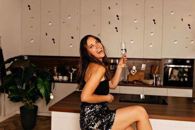 Lächelnde frau, die in der küche mit hellem make-up und welligem haar sitzt und ein glas wein hält