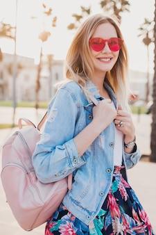 Lächelnde frau, die in der stadtstraße im stilvollen bedruckten rock und in der übergroßen jeansjacke mit rosa sonnenbrille geht