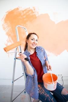 Lächelnde frau, die innenwand des hauses malt. renovierungs-, reparatur- und renovierungskonzept.