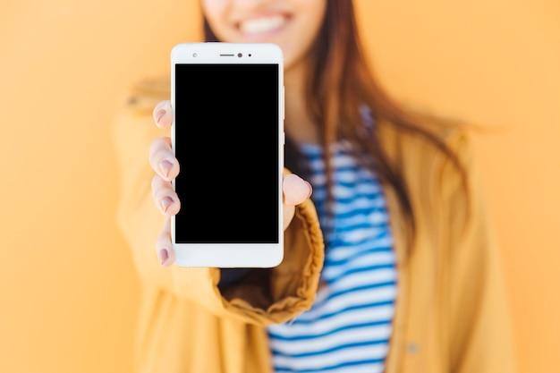 Lächelnde frau, die intelligentes telefon des leeren bildschirms gegen gelben hintergrund zeigt