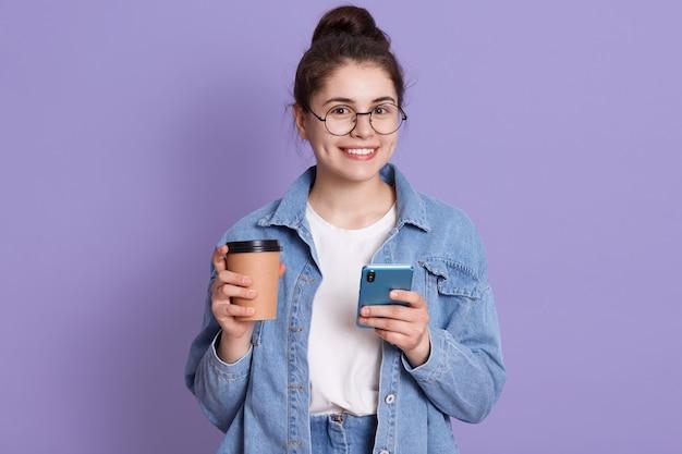 Lächelnde frau, die jeansjacke, weißes hemd und runde brille trägt, teenager-mädchen hält kaffee und handy zum mitnehmen