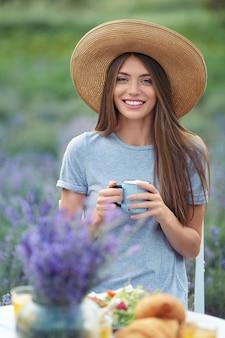 Lächelnde frau, die kaffee im lavendelfeld genießt