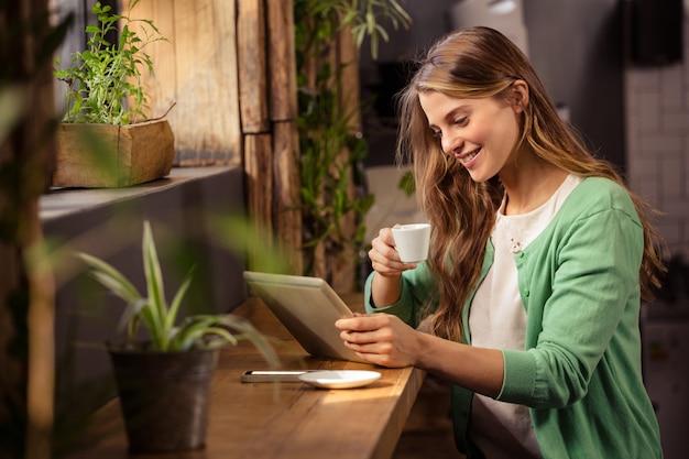 Lächelnde frau, die kaffee trinkt und tablette benutzt