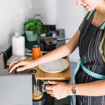 Lächelnde frau, die kaffee von der espresso-kaffeemaschine in der küche nimmt