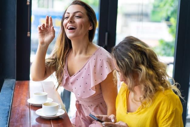 Lächelnde frau, die kellner anruft und mit freund im café sitzt
