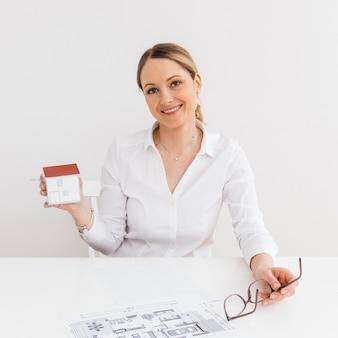 Lächelnde frau, die kleines papierhausmodell am arbeitsplatz zeigt