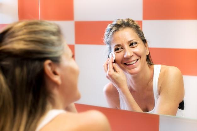 Lächelnde frau, die make-up entfernt
