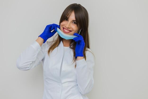 Lächelnde frau, die mit chirurgischer maske und handschuhen aufwirft