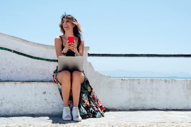 Lächelnde frau, die mit dem handy tippt, während sie mit laptop auf der straße arbeitet