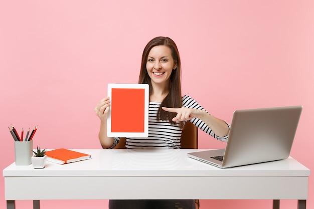 Lächelnde frau, die mit dem zeigefinger auf einen tablet-computer mit leerem bildschirm zeigt, sitzt am weißen schreibtisch mit einem modernen pc-laptop