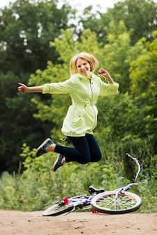 Lächelnde frau, die mit fahrrad im hintergrund springt