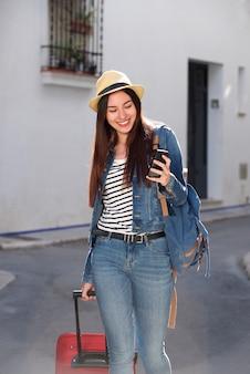 Lächelnde frau, die mit gepäck geht und draußen mobiltelefon hält