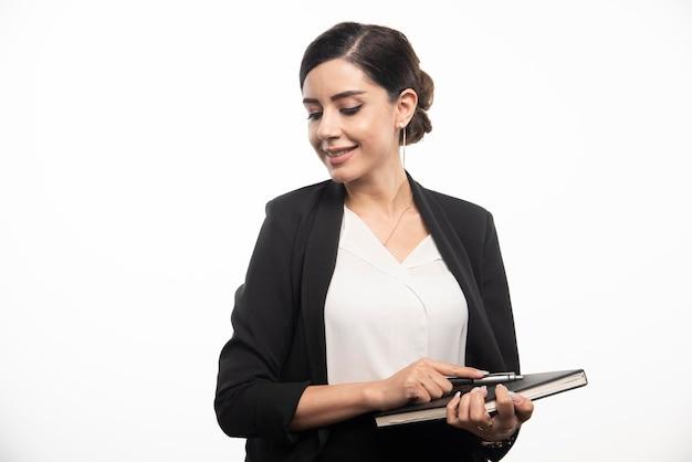 Lächelnde frau, die mit notizbuch auf weißem hintergrund aufwirft. foto in hoher qualität