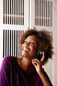 Lächelnde frau, die musik auf kopfhörern hört