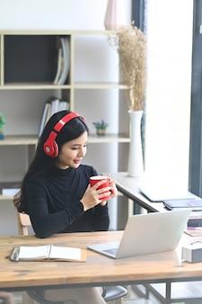 Lächelnde frau, die musik im kopfhörer hört und kaffee im büro trinkt.