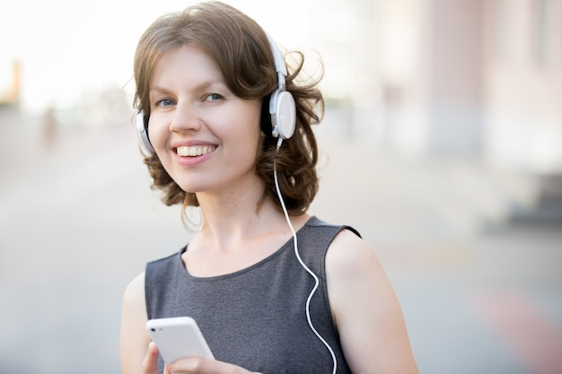 Lächelnde frau, die musik online genießt
