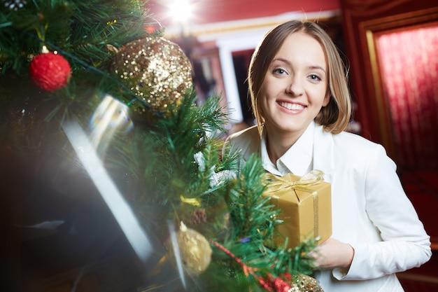 Lächelnde frau, die neben einem weihnachtsbaum