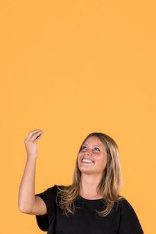 Lächelnde frau, die oben schaut und auf gelben wandhintergrund gestikuliert