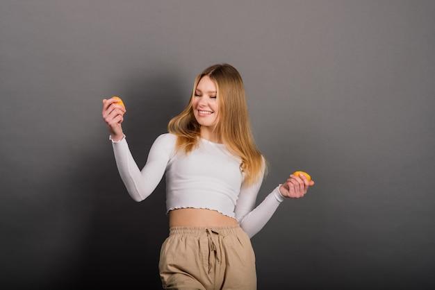 Lächelnde frau, die orange, halbe frucht, langes haar isst. studioaufnahme