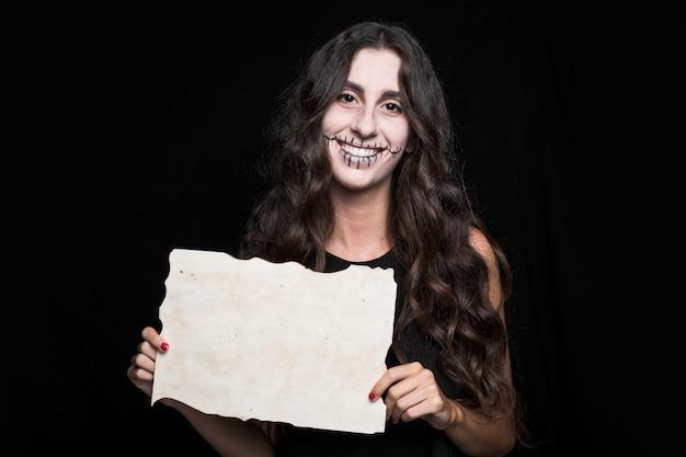 Lächelnde frau, die papier hält