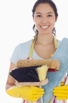 Lächelnde frau, die reinigungswerkzeuge hält