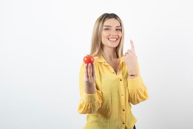 Lächelnde frau, die rote tomate hält und ihre zunge auf weiß herausstreckt.