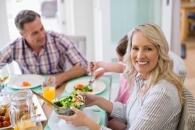 Lächelnde frau, die schüssel salat auf esstisch hält