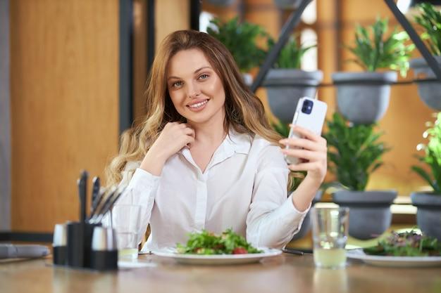 Lächelnde frau, die selfie auf modernem telefon tut