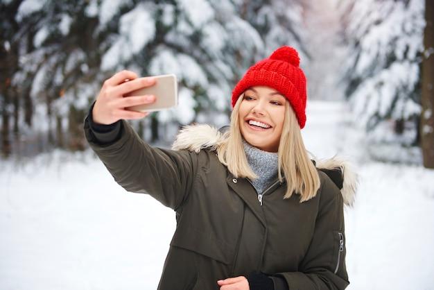 Lächelnde frau, die selfie im winterwald macht