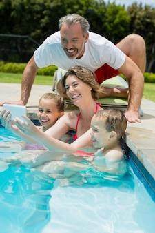 Lächelnde frau, die selfie mit familie im schwimmbad nimmt