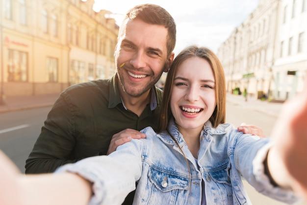 Lächelnde frau, die selfie mit ihrem freund auf straße nimmt