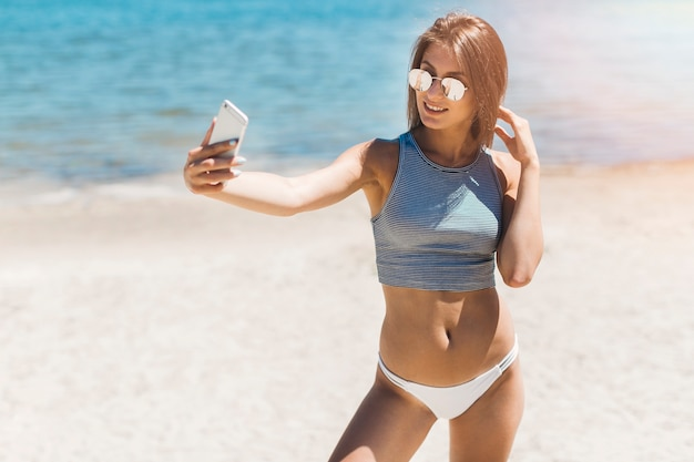 Lächelnde frau, die selfie nahe meer nimmt