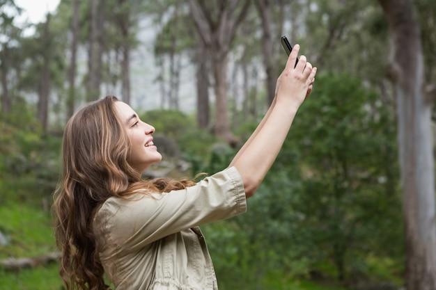 Lächelnde frau, die selfies nimmt