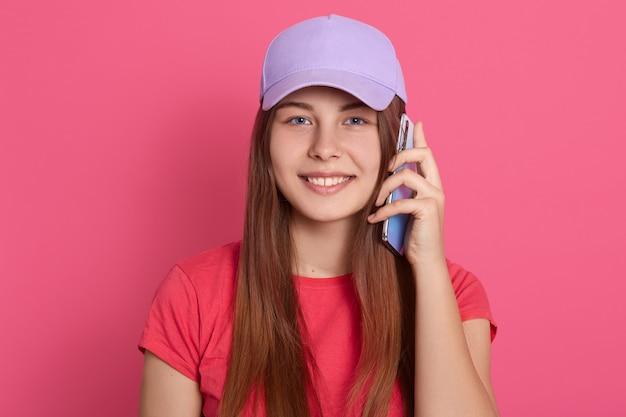 Lächelnde frau, die smartphone nahe ihrem ohr hält und lächelnd schaut, rotes lässiges t-shirt und baseballmütze tragend, gegen rosa wand stehend.