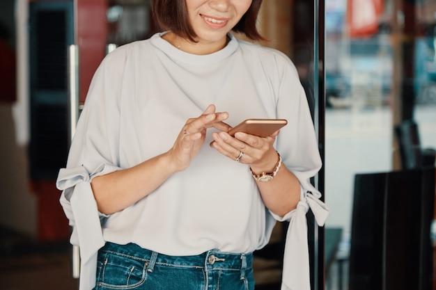 Lächelnde frau, die smartphone überprüft