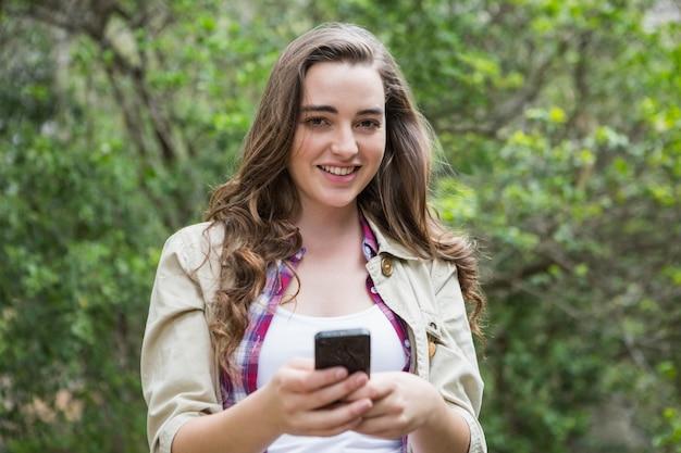 Lächelnde frau, die smartphone verwendet